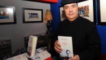 الكاتب والصحفي التونسي توفيق بن بريك مع أحد إصداراته عام 2011 (فرانس برس)