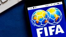 In this photo illustration a FIFA logo seen displayed on a...