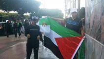 متظاهرة جزائري يرفع العلم الفلسطيني