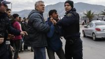 شرطي يعتقل مهاجراً على جزيرة ليسبوس- الأناضول