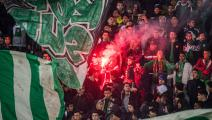 """Supporters of Raja Club Athletic light up a flare as they chant slogans and wave their flags during a Moroccan Botola football match between Raja and Mouloudia Oujda in Casablanca on January 22, 2020. - From Casablanca to Algiers via Tunis, the chants belted out across football stadiums echo young North African fans' frustrations unrelated to the highs and lows of the beautiful game itself. Chants of """"F'bladi delmouni!"""" (""""Oppressed in my country!"""") at the demonstrations that have been commonplace in Algeria"""