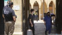 طالب وعاملة وموظفا أمن على باب الجامعة الأميركية في بيروت (حسين بيضون)