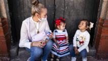 تتحدث إلى طفلتيها (ألفريدو مارتينيز/ Getty)