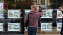 سيدة تتفحص أسعار المنازل بإحدى الوكالات العقارية بلندن