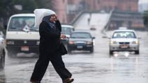 امرأة مصرية تحت المطر في القاهرة (أحمد حسن/ فرانس برس)