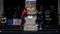 طلّاب فنون يلصقون لوحات احتجاجية أمام أحد المسارح في مدينة ليون، منتصف آذار/ مارس الجاري (Getty)