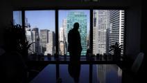 """مدير أحد صناديق الاستثمار ينظر إلى سوق """"وول ستريت"""" من مكتبه"""