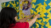 إلصاق فراشات على جدار مكتبة بمدينة المكسيك في الذكرى الأولى لرحيل ماركيز (Getty)
