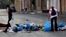 مواطنون يزيلون القمامة من أحد شوارع بيروت/ فرانس برس