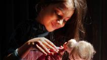طفلة تلعب بدمية باربي (رنا ساجد حسين/ Getty)