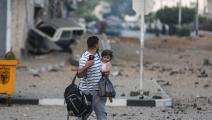 فلسطيني يحمل ابنته وبعض حاجيّاته وهاتفه في غزة (علي جاد الله/الأناضول)