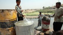 يعبّئ المياه من نهر ديالى (أحمد الربيعي/ فرانس برس)