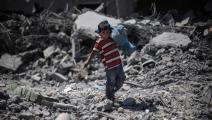 """طفل فلسطيني يحمل لعبته في بيت حانون بغزّة بعد """"وقف إطلاق النار""""، 11 أغسطس/ آب 2014 (Getty)"""