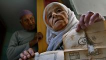 لاجئة فلسطينية في مخيّم بلاطة قرب نابلس تعرض وثائق ملكية بيت عائلتها الذي احتل عام 1948 (Getty)