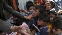 أطفال يتدافعون للحصول على وجبة غداء في اليمن (محمد حمود/ Getty)