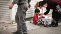 مسنّة تركية تطعم طفلاً سورياً في أنقرة (توناهان تورهان/ Getty)