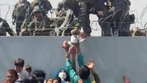 أب يسلم طفله الرضيع إلى جنود في أفغانستان بعدسة مصور رويترز عمر حيدري (تويتر)
