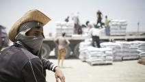 فلسطينيون يفرغون شاحنة إسمنت بعد دخولها غزة من معبر رفح الحدودي مع مصر (فرانس برس)