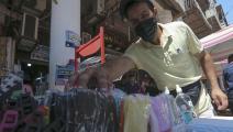 صاحب متجر يرتب أقنعة الوجه الطبية في أحد أسواق بغداد (فرانس برس)