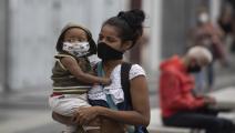أم وطفلتها ترتديان الكمامة/مجتمع (ليوناردو فيرنانديز فيلوريا/ Getty)