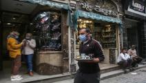 مصريون يضعون الكمامات في شارع المعز بالقاهرة (Getty)