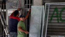 إصلاح واجهة مصرف تعرض للتخريب (حسين بيضون/العربي الجديد)