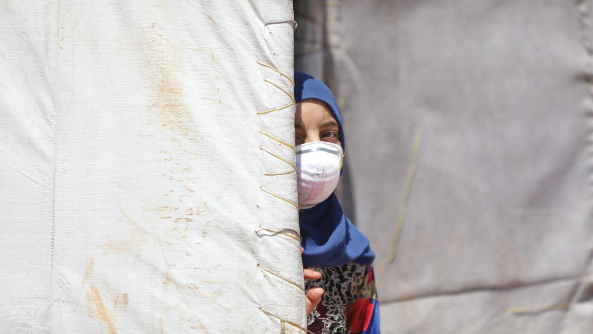 Daily life in refugee camps in Idlib IDLIB, SYRIA - JUNE 19: A Syrian girl wearing a medical mask as a precaution against coronavirus (Covid-19) pandemic is seen at a refugee camp where thousands of displaced Syrians shelter due to Assad Regime forces and its allies ongoing attacks over residential areas, in Idlib, Syria on June 19, 2020. Displaced civilians have difficulties in reaching many basic living needs such as food, shelter, education and health in camps. (Photo by Bekir Kasim/Anadolu Agency via Ge