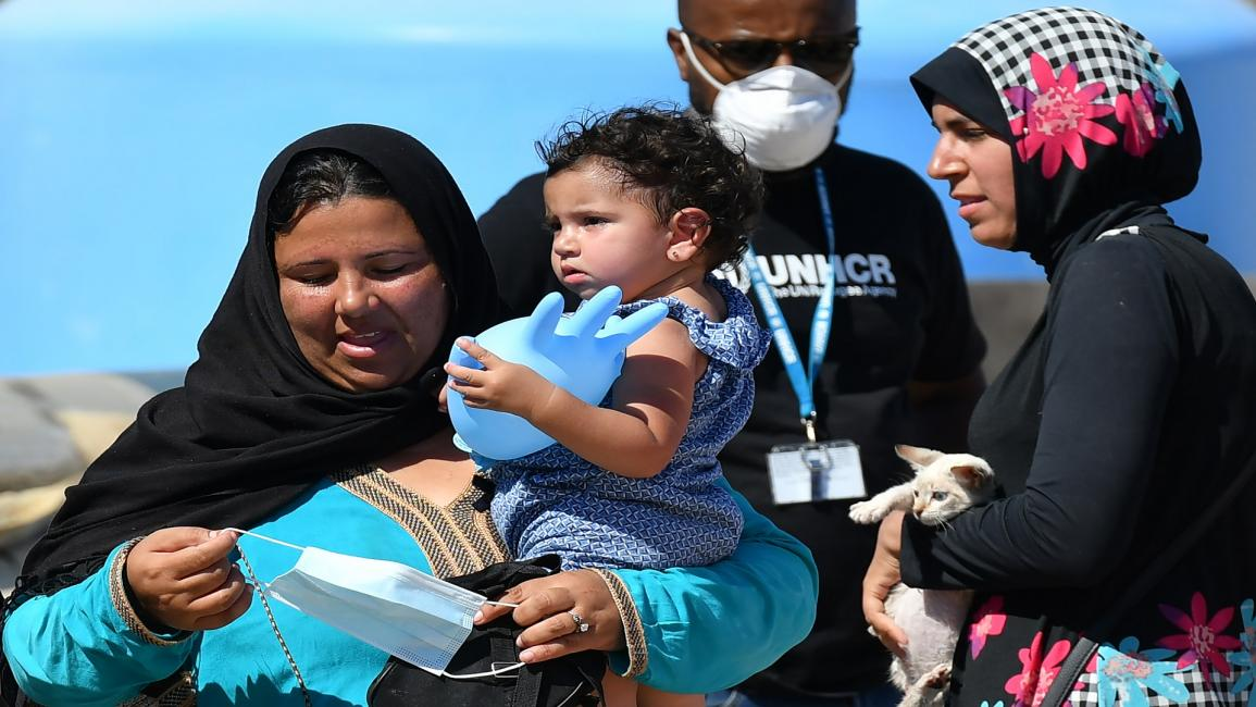 ITALY-EUROPE-MIGRANTS A woman holds a child while another carries a cat before they board a bus after migrants disembark from the Guardia Costiera boat in the Italian Pelagie Island of Lampedusa on July 29, 2020. - Boats with migrants mainly from Tunisia continue to arrive on the Italian island of Lampedusa. Intercepted by the boats of the Italian costal guard and guardia di finanza police before reaching the shore, migrants are escorted on the Island and transferred to the island's reception centre. (Photo