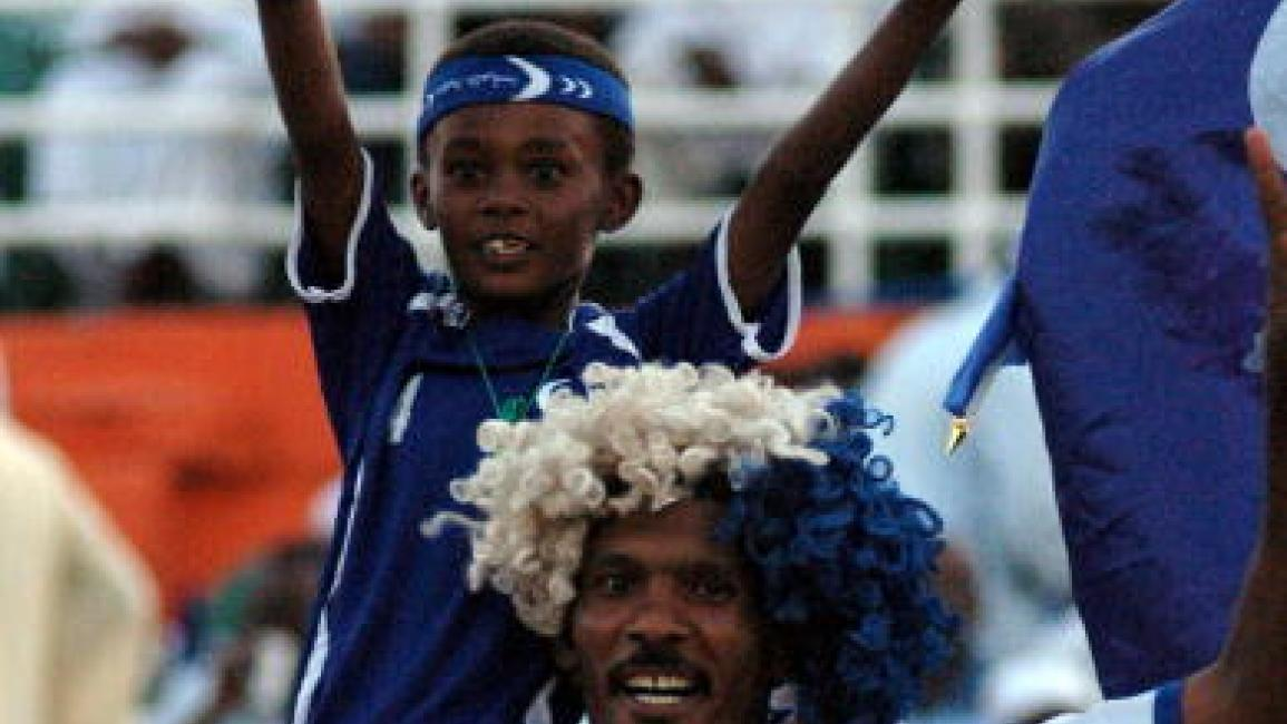 A Sudanese boy and his father cheer for al-Hilal during their African Champions League football match against Zambia's Zesco United in Khartoum late on July 31, 2009. Hilal won 1-0. AFP PHOTO/ASHRAF SHAZLY (Photo credit should read ASHRAF SHAZLY/AFP via Getty Images)